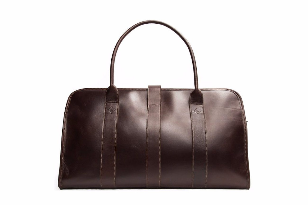 Description. Navy and black Fabric + Leather Weekender from Troubadour featuring a top zip closure, a main internal compartment, an internal zipped pocket, top handles, a detachable and adjustable shoulder strap and main external pocket with elegant window construction.