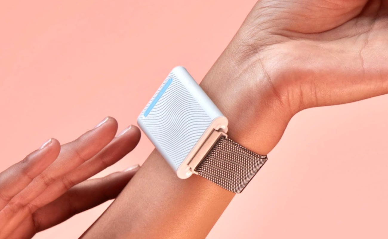 The wearable personal thermostat is on a person's wrist.