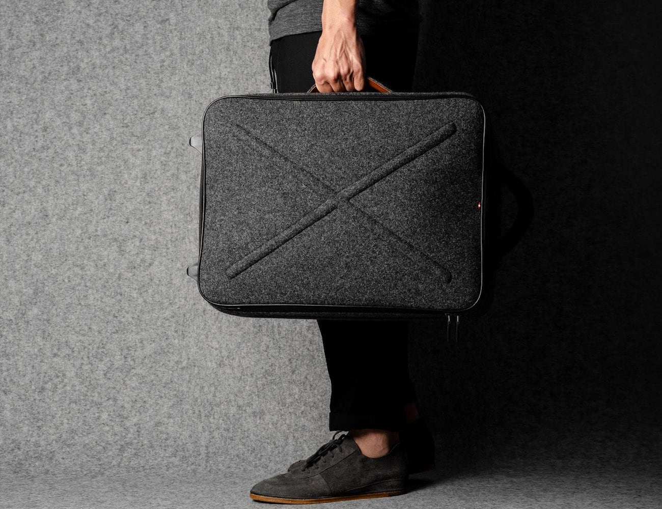 A person is holding the hardgraft Worldly Cabin Suitcase by its side handle.