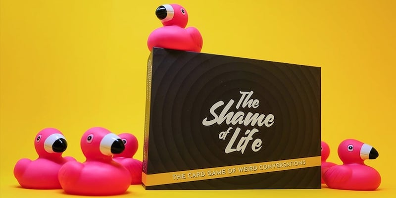 A naughty party game box against a yellow background with pink flamingo rubber ducks around it.