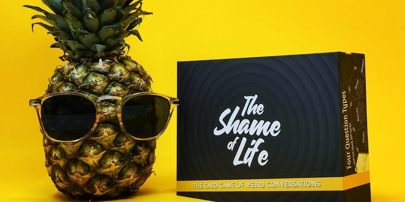 A naughty party game against a yellow background, and a pineapple with sunglasses on it is sitting next to it.