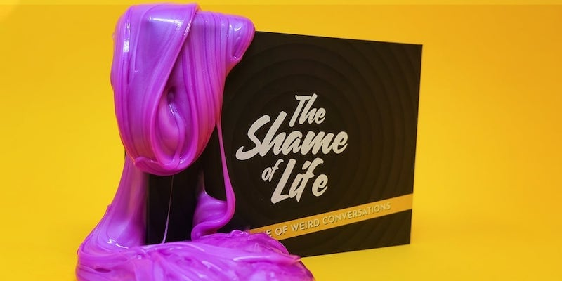 """Purple slime is dripping off the corner of a black game box that says """"The Shame of Life."""""""
