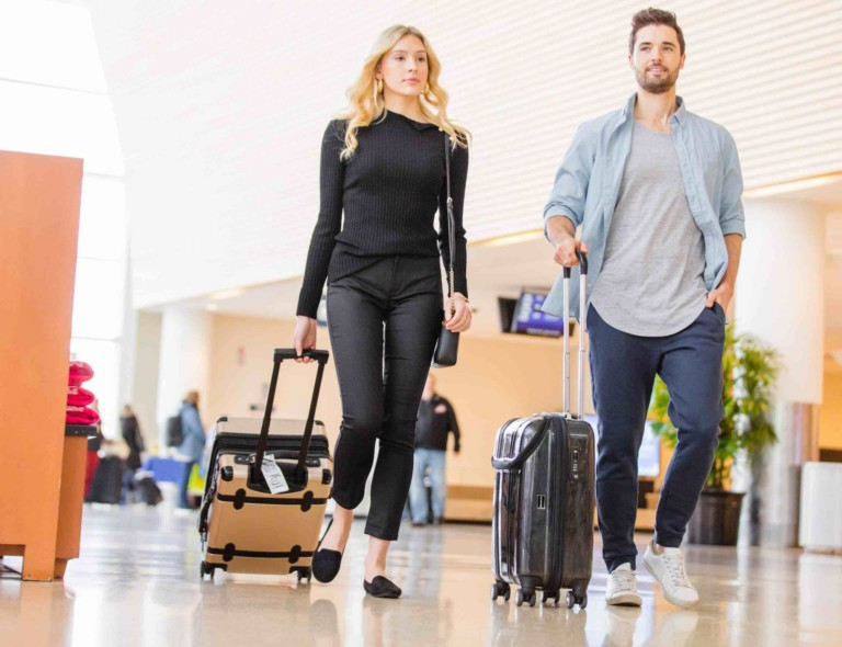 Man and woman lugging rolling suitcases through an airport