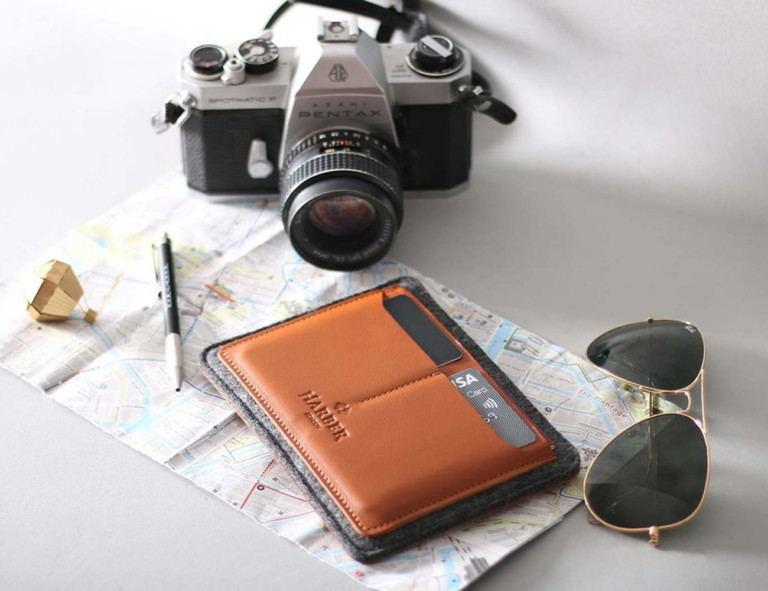 Wool and leather passport wallet on top of a map with a camera