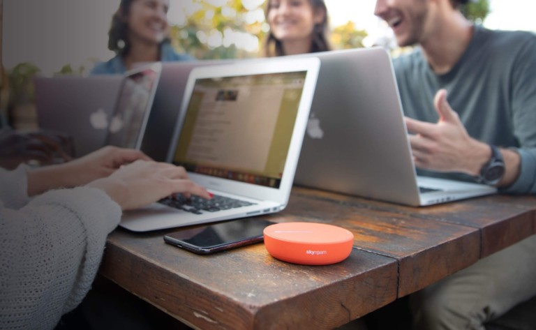 Orance disc-shaped device on a table with a laptop