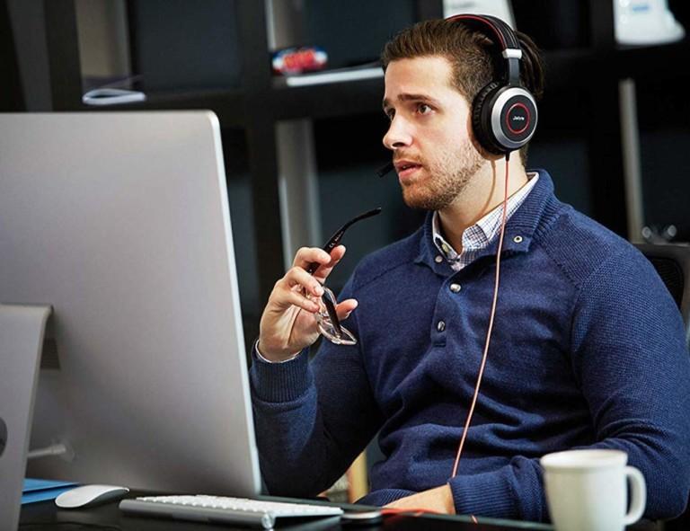 Person in office wearing JABRA headphones