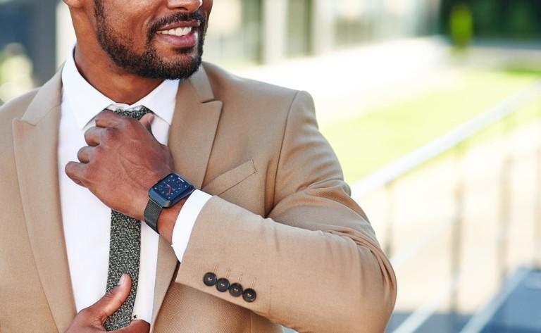 A man in a tan suit wearing cool tech gadgets from Kickstarter fitness watch.