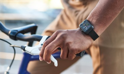 A man's hand clutching a bicycle break while wearing a cool tech gadgets from Kickstarter fitness watch.