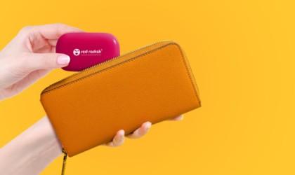 A woman putting a cool tech gadgets from Kickstarter charger pod into a brown wallet.