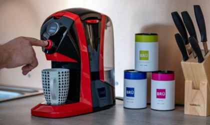 A red cool tech gadgets from Kickstarter tea brewer with canisters next to it.