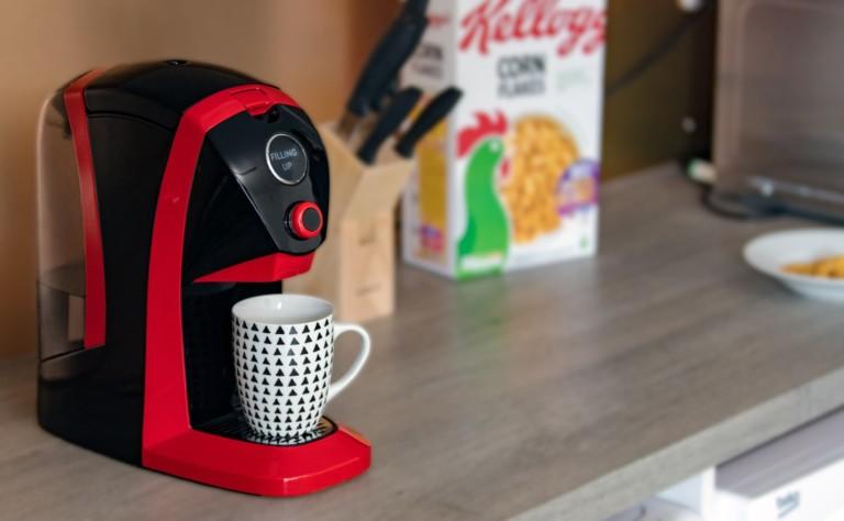 A red cool tech gadgets from Kickstarter tea maker with a mug on a kitchen counter.