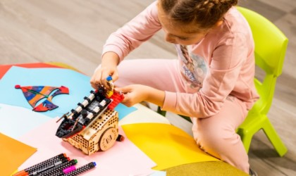 A girl sitting on the floor using LEGOs on a cool tech gadgets from Kickstarter coding robot.
