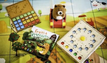 A book, a set of blocks, a stuffed bear, and a coding machine from cool tech gadgets from Kickstarter coding game.