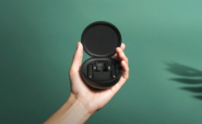 A hand holding a case of cool tech gadgets from Kickstarter earbuds against a green background.