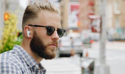 A man wearing cool tech gadgets from Kickstarter earbuds.