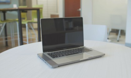 An open MacBook with a cool tech gadgets from Kickstarter hub case attached to the bottom.