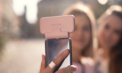 Close up of a woman holding a pink cool tech gadgets from Kickstarter camera on her phone.