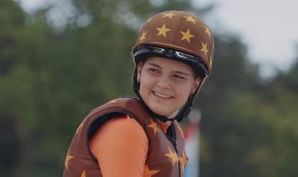 A girl wearing a helmet with a cool tech gadgets from Kickstarter camera attached.