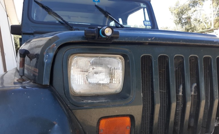 A Jeep with a cool tech gadgets from Kickstarter light attached above the headlight.
