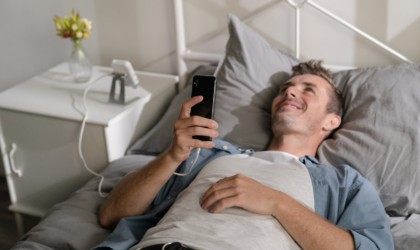 A man laying in bed with a phone, a cool tech gadgets from Kickstarter mini projector is on the nightstand next to him.