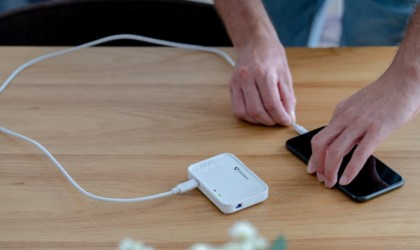 A hand plugging in a cool tech gadgets from Kickstarter mini projector to a smartphone.