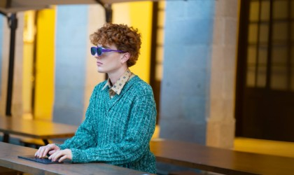 A person wearing a pair of cool tech gadgets from Kickstarter glasses, sitting at a table.