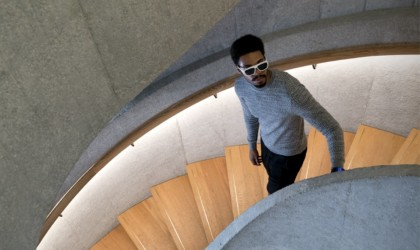 A man on a spiral staircase wearing a pair of cool tech gadgets from Kickstarter glasses.