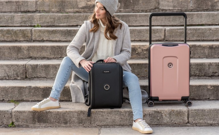 A woman sitting on steps with cool tech gadgets from Kickstarter suitcases, one black and one pink.