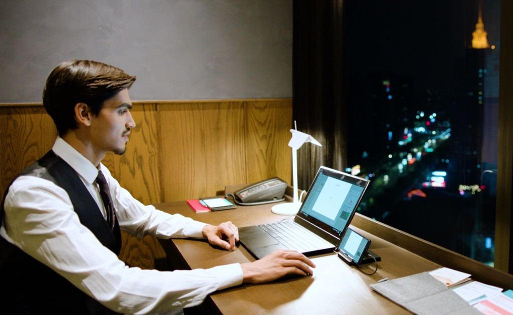 A man sitting at a desk using a new tech gadgets laptop device.