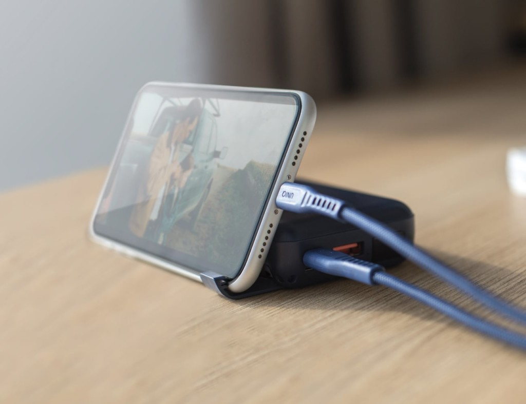 A phone plugged into and propped up on a new tech gadgets charger.