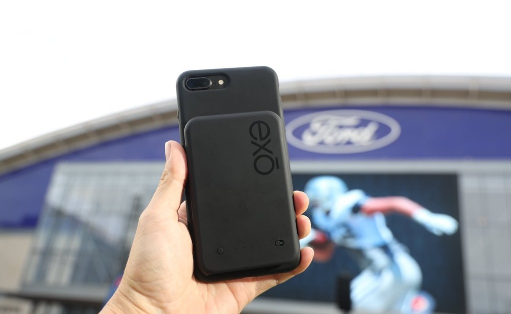 A person holding a phone with a new tech gadgets charger attached to the back of it.
