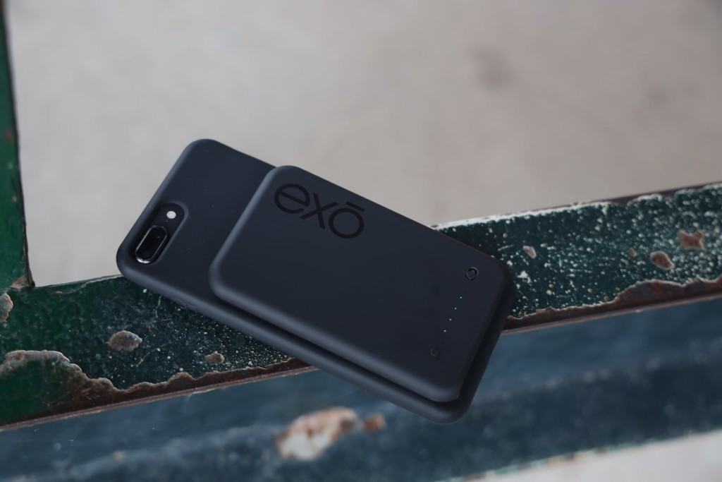 A black phone with a new tech gadgets magnetic charger on the back.