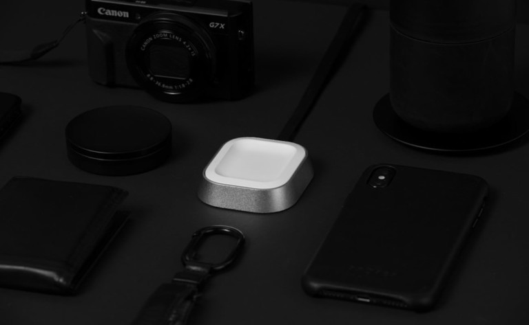 A small square new tech gadgets AirPods charger on a table with tech items around it.