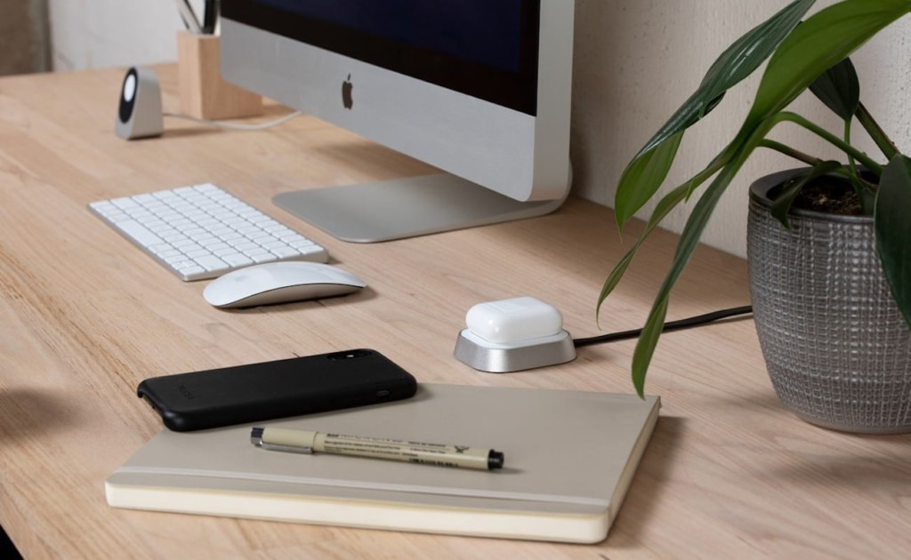A small new tech gadgets charger on a desk with AirPods on it.