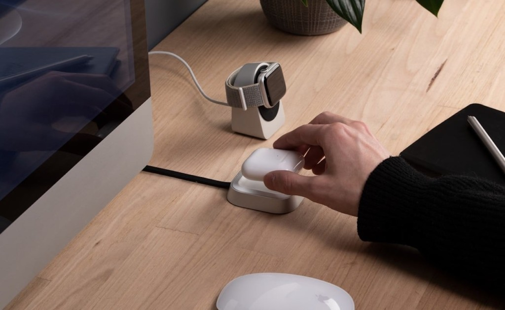 A hand putting a pair of AirPods on a new tech gadgets charger.