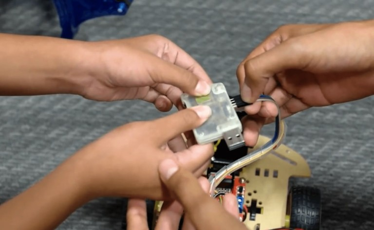 Multiple sets of kids' hands installing a new tech gadgets voice control dongle.