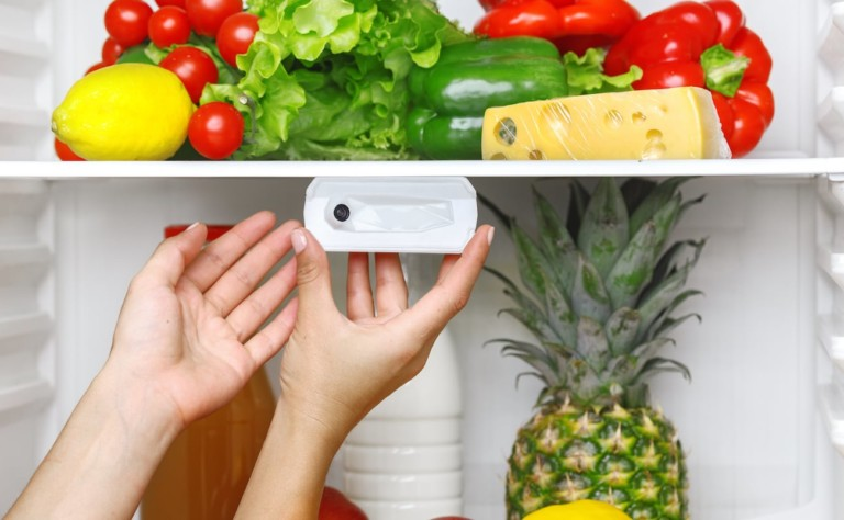 A pair of hands attaching a new tech gadgets refrigerator camera in a fridge.