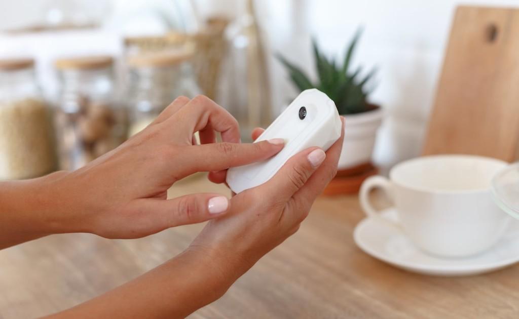 A pair of hands holding a new tech gadgets refrigerator camera