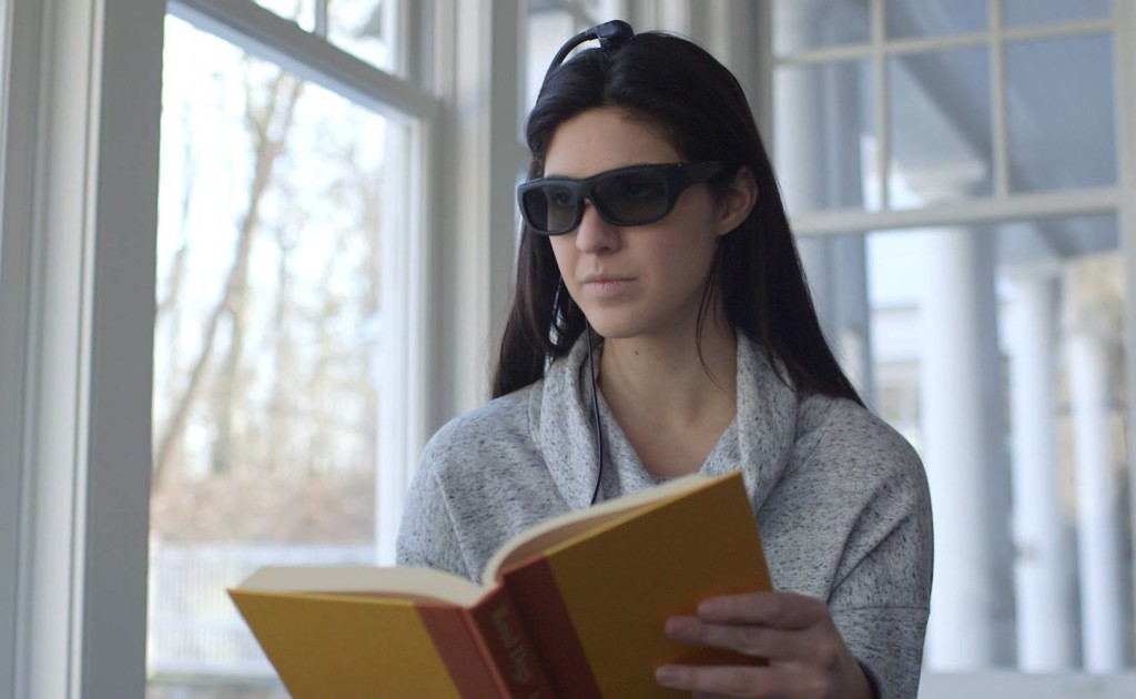 A woman reading a book, wearing a new tech gadgets pair of glasses.