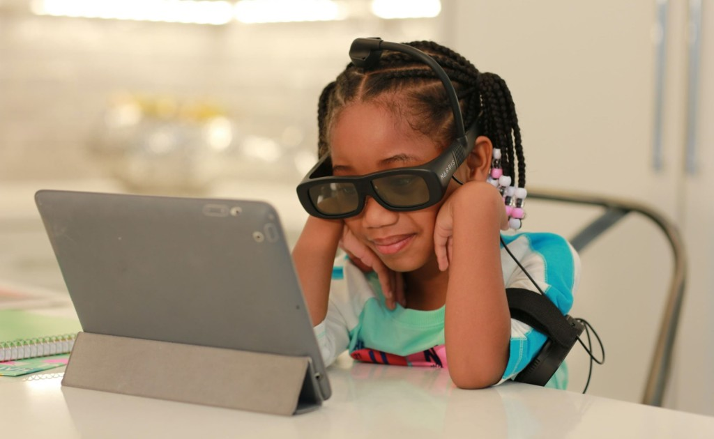 A little girl looking at a tablet wearing a pair of new tech gadgets glasses.