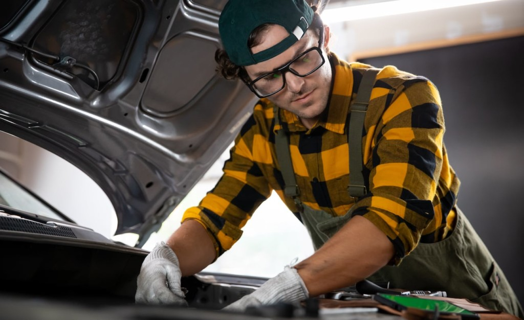 A man working on a car, wearing a pair of new tech gadgets glasses.