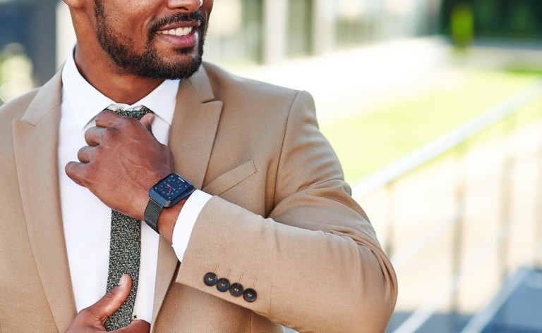 A man in a suit, wearing a new tech gadgets smart watch.