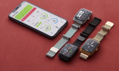 Three new tech gadgets smart watches and a phone on a red background.