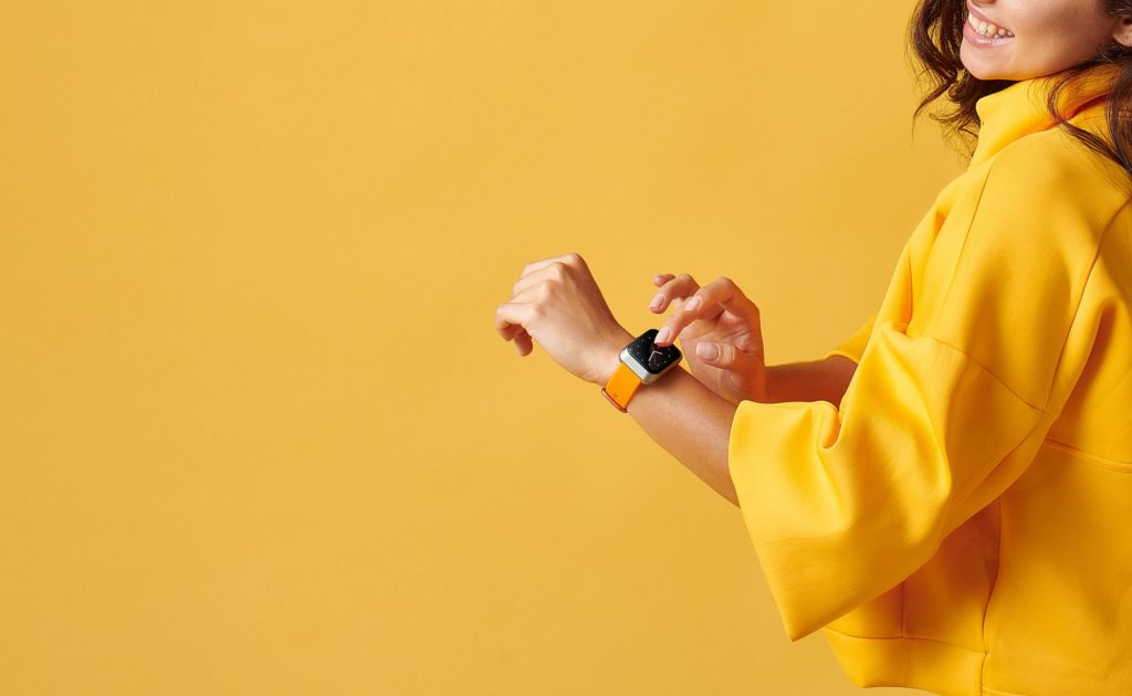 A woman wearing a new tech gadgets smart watch against a yellow background.