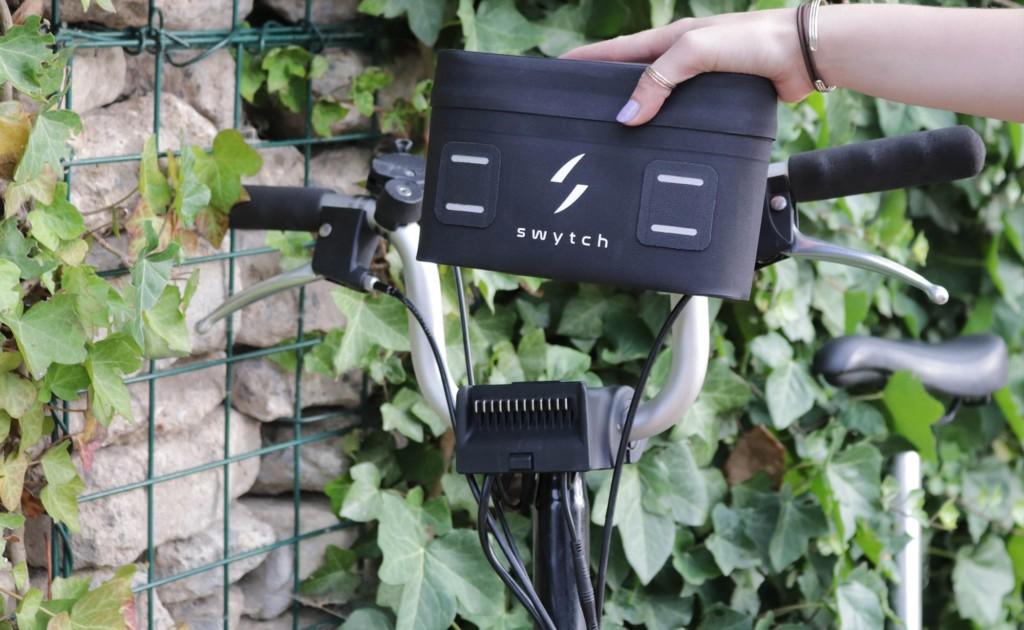 A hand putting a new tech gadgets electric bike pack on a bike.