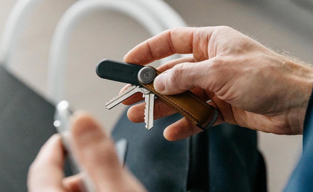 A hand holding a set of keys with a black new tech gadgets tracker on them.