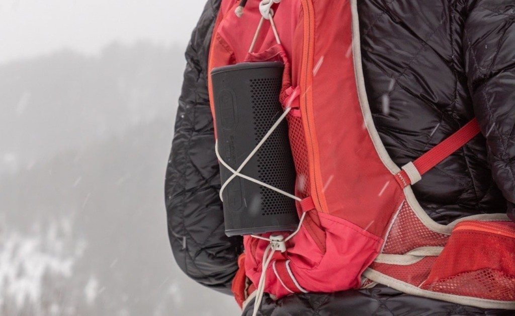 A wireless speaker shaped like a black tube attached to a red backpack.