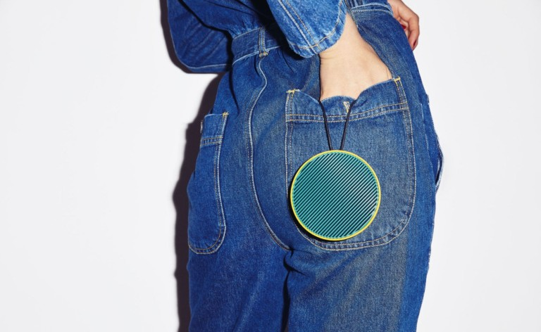 A round blue wireless speaker hanging from a woman's back jeans pocket.