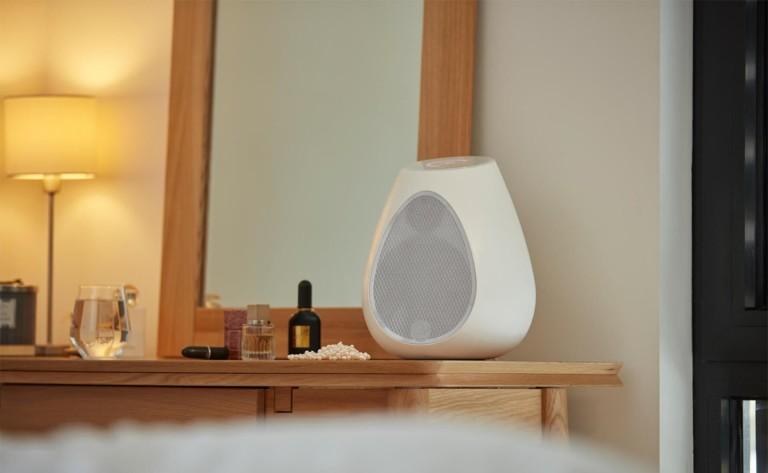 A white, egg-shaped wireless speaker sitting on a dresser.