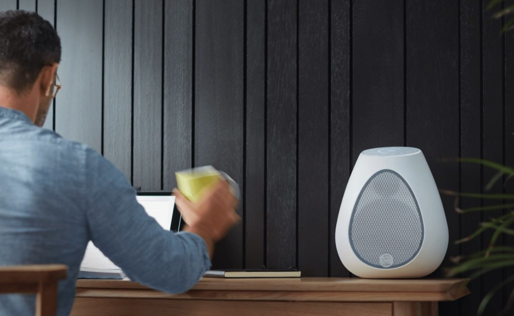 A white, egg-shaped speaker on a table with someone lifting up a mug next to it.
